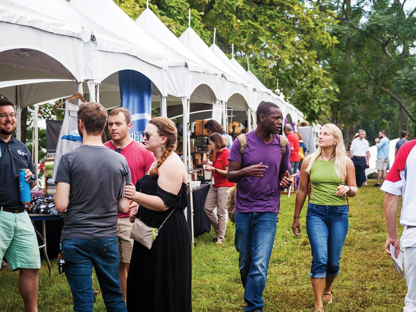 Groups of young people outside a row of tents at the Heritage Harvest Festival.