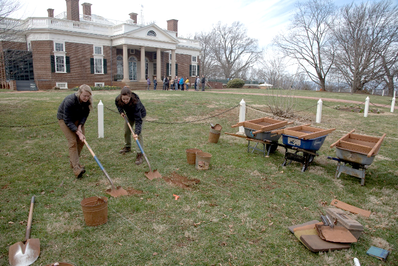 """Figure 1. Archaeologists Cameron Wooddell and Elizabeth Donison begin excavating a 5-foot quadrat just outside the post-and-chain fence that surround what Jefferson called """"the semi-oval level"""". Excavation revealed deposits of brick bats and sediment, over three feet deep, derived from the the demolition of Monticello I and extensive leveling on the ground surface associated with the construction of Monticello II."""